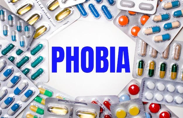 La parola phobia è scritta su uno sfondo chiaro circondato da confezioni multicolori con pillole. concetto medico