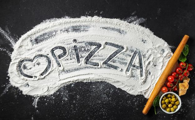 La parola pizza e cuore è scritta su farina con mattarello e ingredienti per fare la pizza italiana, vista dall'alto. sfondo astratto di cottura