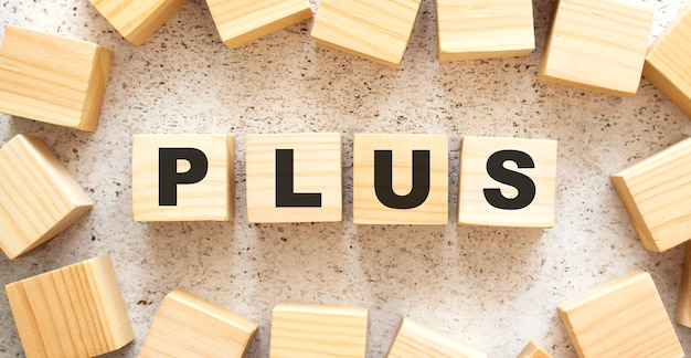 La parola plus è composta da cubi di legno con lettere, vista dall'alto su sfondo chiaro. spazio di lavoro.