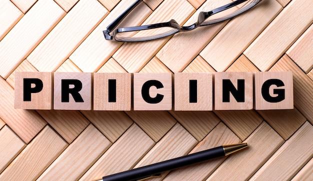 La parola prezzo è scritta su cubi di legno su una superficie di legno accanto a una penna e occhiali