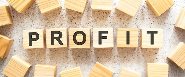 La parola profit è composta da cubi di legno con lettere, vista dall'alto su sfondo chiaro. spazio di lavoro.