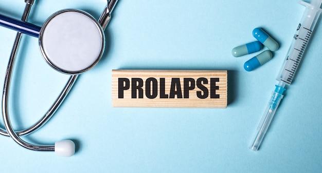 La parola prolaps è scritta su un blocco di legno su sfondo blu vicino allo stetoscopio, alla siringa e alle pillole. concetto medico