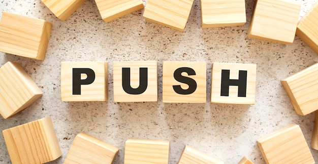La parola push è composta da cubi di legno con lettere, vista dall'alto su sfondo chiaro. spazio di lavoro.