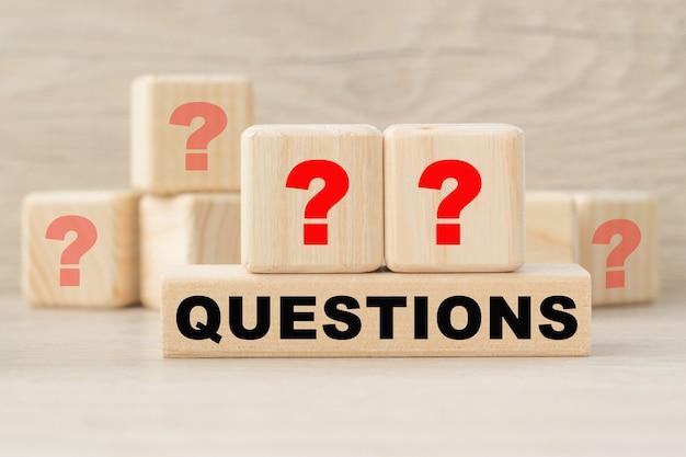 La parola domande e punti interrogativi sono scritti su cubi di legno