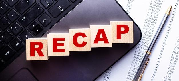 La parola recap è scritta su cubi di legno sulla tastiera accanto alla penna.