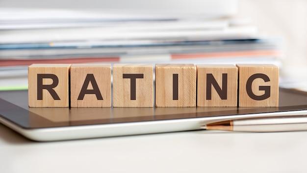 La parola ridurre è scritta su cubi di legno in piedi su un tablet, in superficie una pila di documenti