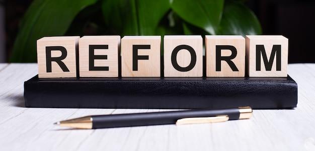 La parola reform è scritta sui cubi di legno dell'agenda vicino al manico