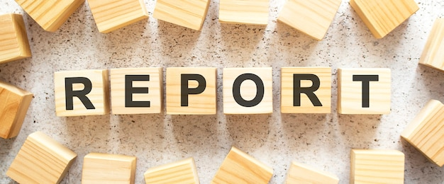 La parola report è composta da cubi di legno con lettere, vista dall'alto su una superficie chiara
