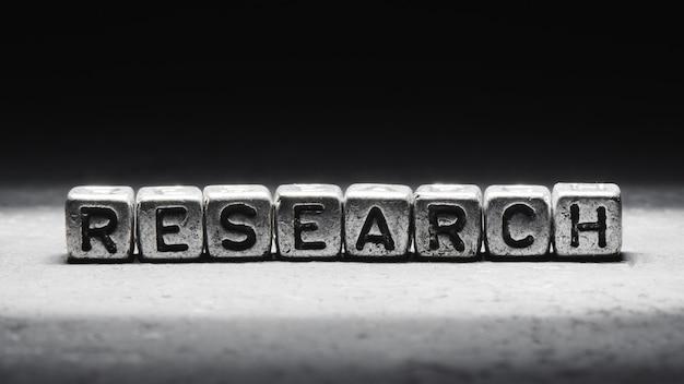 La parola ricerca sui cubi di metallo su sfondo nero