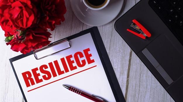 La parola resilienza è scritta in rosso su un blocco note bianco vicino a un laptop, caffè, rose rosse e una penna