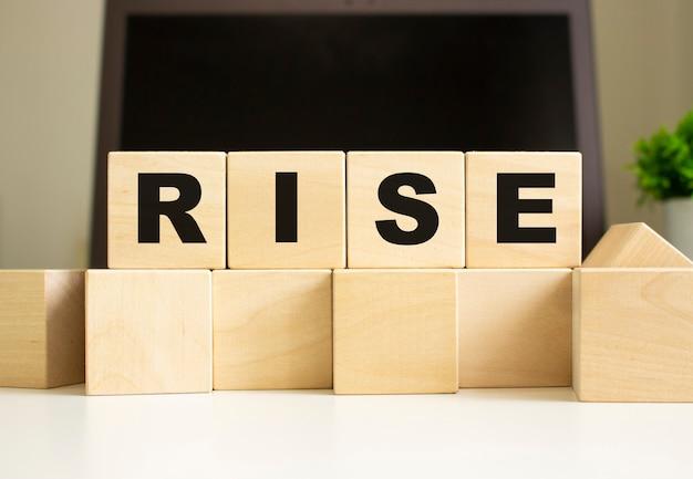 La parola rise è scritta su cubi di legno che giacciono sul tavolo dell'ufficio davanti a un laptop. concetto di affari.