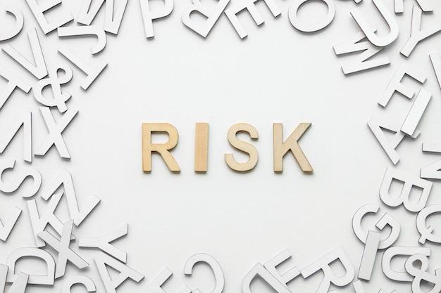 Alfabeto di legno di rischio di parola su fondo bianco.