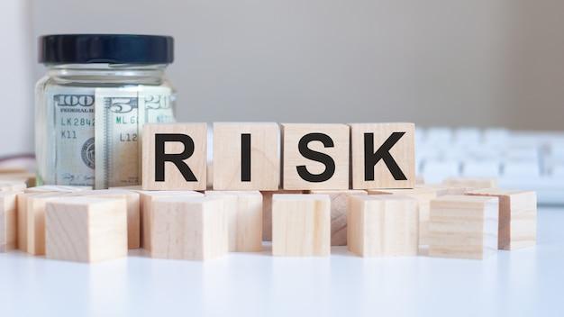 La parola rischio sui blocchi di legno e una banca con i soldi