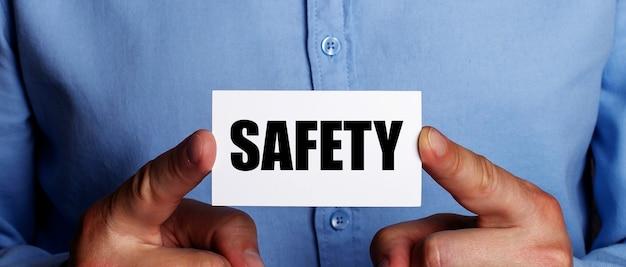 La parola sicurezza è scritta su un biglietto da visita bianco nelle mani di un uomo. concetto di affari