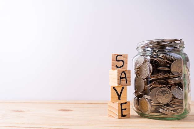 Salvataggio di parole scritte su blocchi di legno impilati accanto a un barattolo di vetro con monete su un tavolo di legno e un muro bianco