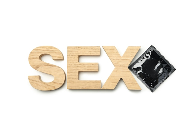 Parola sesso fatta di lettere in legno e preservativo su sfondo bianco