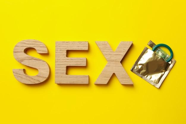 Parola sesso fatta di lettere di legno e preservativo sulla superficie gialla