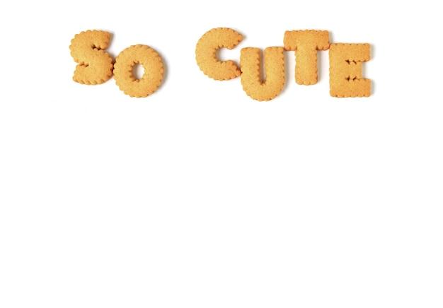 La parola così carina scritta con biscotti alfabeto su bianco con spazio libero per il design