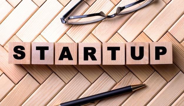 La parola startup è scritta su cubi di legno su una parete di legno accanto a una penna e occhiali.