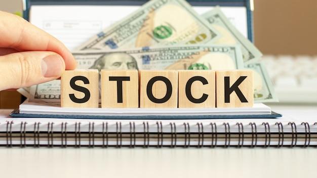 Stock di parola, concetto di affari su cubi di legno e sfondo di dollari