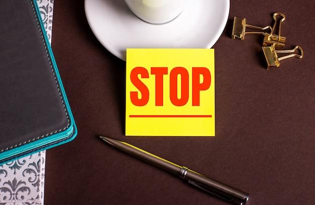La parola stop scritta su carta gialla su sfondo marrone vicino a una tazza di caffè e diari