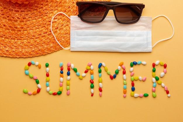 Parola estate scritta con caramelle colorate su sfondo arancione con maschera protettiva