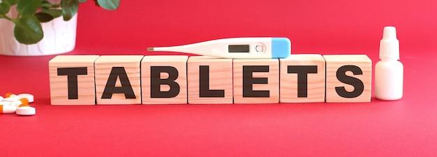 La parola compresse è composta da cubi di legno su sfondo rosso con farmaci.