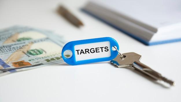 La parola obiettivi è scritta su un portachiavi blu. la chiave è sulla scrivania dell'ufficio. sullo sfondo, la mano di una donna tiene in mano banconote