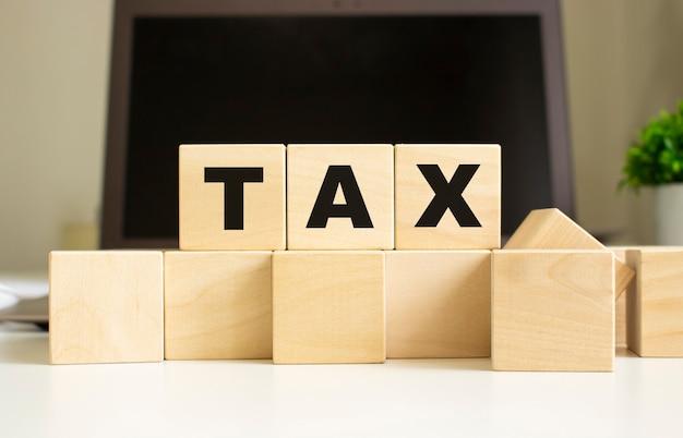 La parola tax è scritta su cubi di legno sdraiati sul tavolo dell'ufficio davanti a un laptop.
