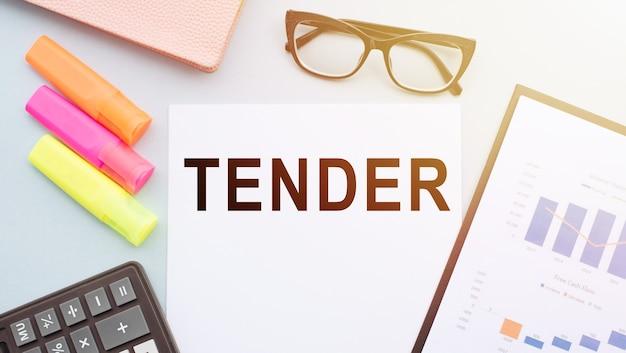 La parola tender sulla scrivania in ufficio con calcolatrice, pennarelli, bicchieri e grafici finanziari