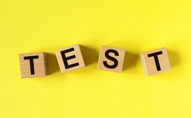 Test di parole su cubi di legno su sfondo giallo brillante