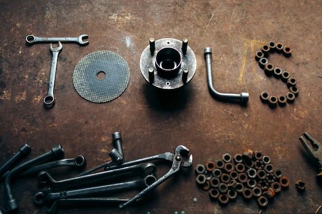 Strumenti di parola realizzati da chiavi, dadi e bulloni sulla scrivania di metallo arrugginito