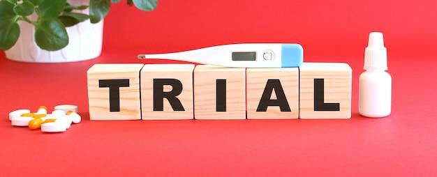 La parola trial è composta da cubi di legno su sfondo rosso con farmaci.