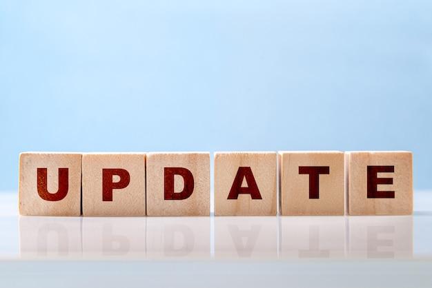 La parola aggiornamento è scritta su blocchi di legno su una superficie del desktop lucida su sfondo blu