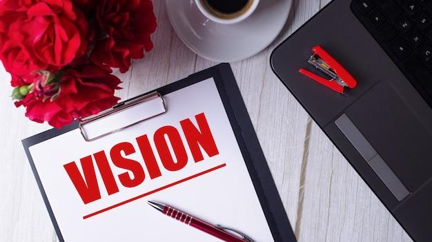 La parola vision è scritta in rosso su un blocco note bianco vicino a un laptop, caffè, rose rosse e una penna