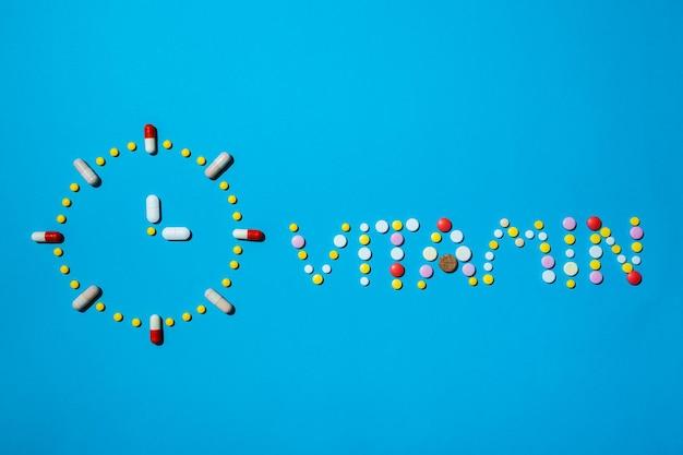 Vitamina di parola scritta con pillole colorate su sfondo blu il concetto di integratore per la salute