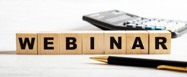 La parola webinar è scritta su cubi di legno tra una calcolatrice e una penna. concetto di affari. defocus