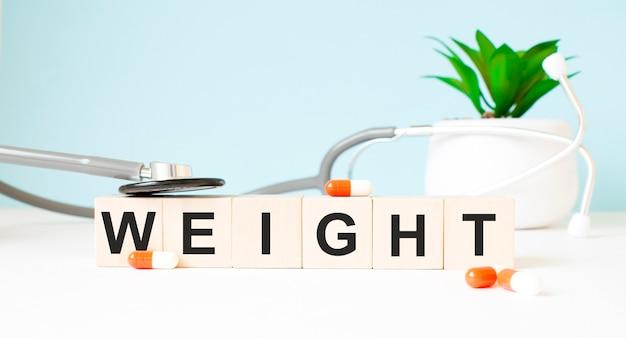 La parola peso è scritta su cubi di legno vicino a uno stetoscopio su uno sfondo di legno. concetto medico