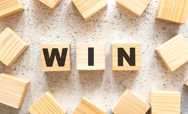 La parola win è composta da cubi di legno con lettere