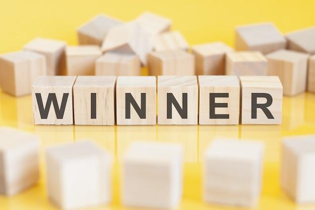 La parola vincitore è scritta su una struttura a cubetti di legno. blocchi su uno sfondo giallo brillante. concetto finanziario. messa a fuoco selettiva. blocchi giocattolo intorno.