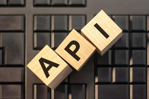 Parole api in 3d lettere dell'alfabeto in legno su uno sfondo di tastiera con spazio di copia.