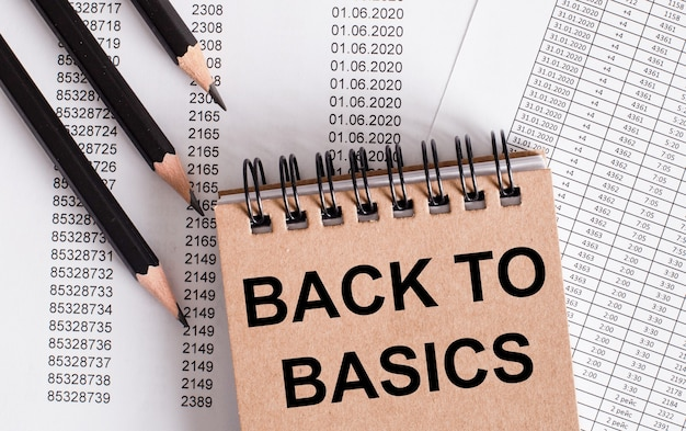 Le parole back to basics sono scritte sul taccuino marrone. matite vicine.