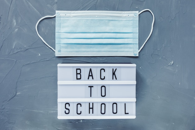 Parole torna a scuola e maschera medica usa e getta su sfondo grigio.