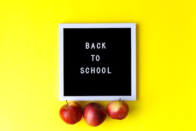 Parole torna a scuola su sfondo giallo. istruzione, torna al concetto di scuola, vista dall'alto, piatto laici