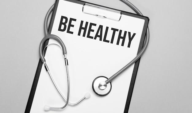 Le parole be healthy sono scritte su carta bianca su uno sfondo grigio vicino a uno stetoscopio.
