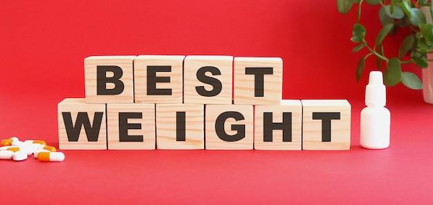La scritta miglior peso è composta da cubi di legno su sfondo rosso con farmaci.