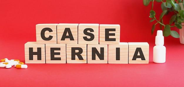 La scritta case hernia è fatta di cubi di legno su fondo rosso con farmaci