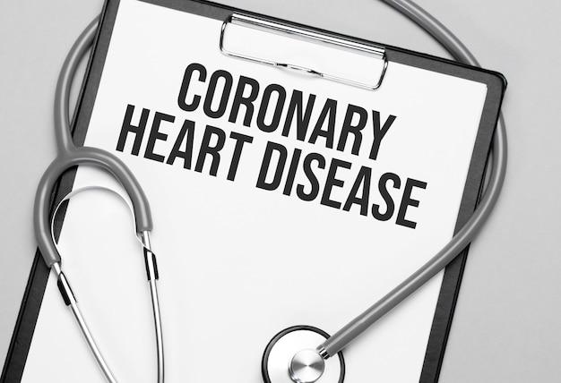 Le parole malattia coronarica è scritta su carta bianca su uno sfondo grigio vicino a uno stetoscopio. concetto medico