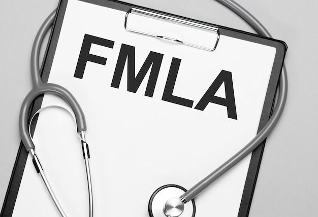 Le parole fmla sono scritte su carta bianca vicino a uno stetoscopio. concetto medico