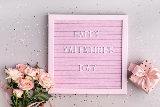 Parole buon san valentino sulla lavagna con lettere in feltro rosa. composizione festiva con un mazzo di rose e una scatola con un regalo su un tavolo grigio. vista dall'alto, piatto. copia spazio.